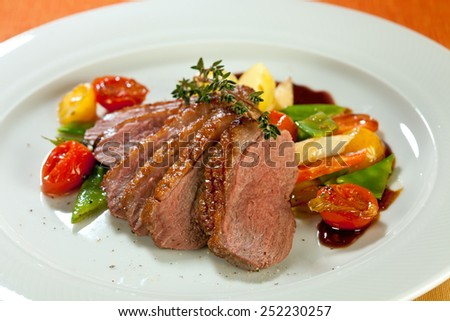 Roasted duck in slices with thyme in port wine sauce, served with cherry tomatoes, sliced potatoes, carrots and asparagus. - stock photo