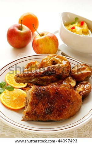 Roasted duck with baked potatoes, apple and orange sauce - stock photo