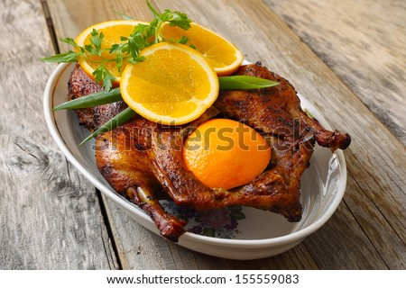 Roasted duck with orange on a wood table - stock photo
