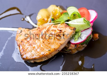 Roasted fish fillet with vegetable salad and fresh vegetables for garnish  - stock photo
