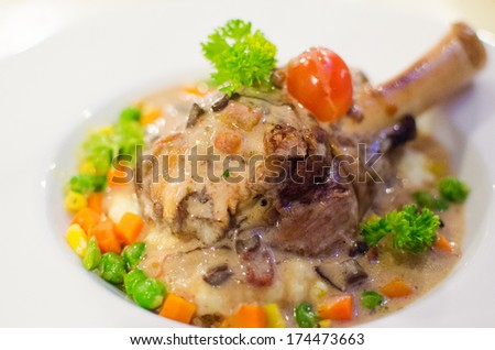 Roasted lamb leg steak on mix vegetables and mashed potato - stock photo