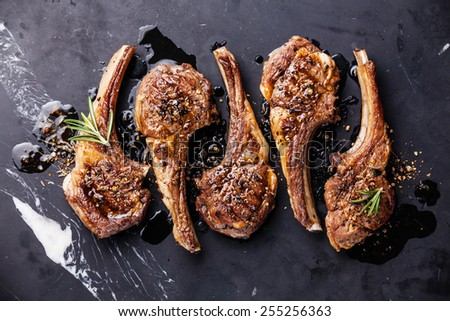 Roasted lamb ribs with spices on black marble background - stock photo