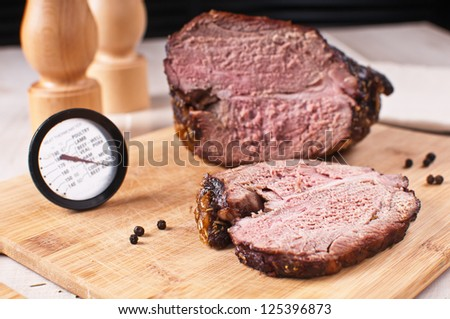 Roasted meat slice and thermometer for cooking - stock photo