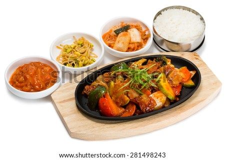Roasted meat with vegetables in a skillet with rice and spicy salad. From a series of Food Korean cuisine. - stock photo