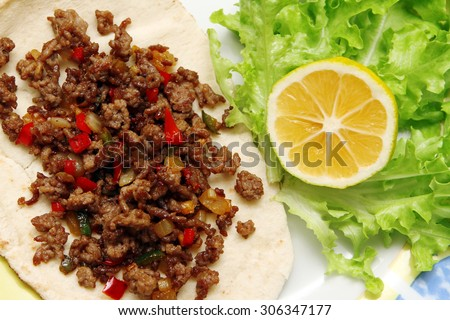 Roasted minced beef with chili pepper on tortilla with lettuce and lemon  - stock photo