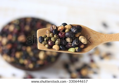 roasted mixed nut. roasted mixed pea. mixed nut. roasted mixed nut in wooden cup or wooden spoon on wooden white background. healthy food. healthy snack. cooked nuts - stock photo