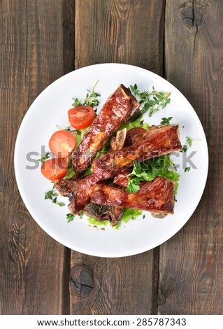 Roasted pork ribs on white plate over wooden table, top view - stock photo
