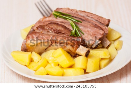 roasted pork ribs with potatoes - stock photo