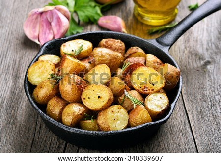 Roasted potato in frying pan on wooden background - stock photo