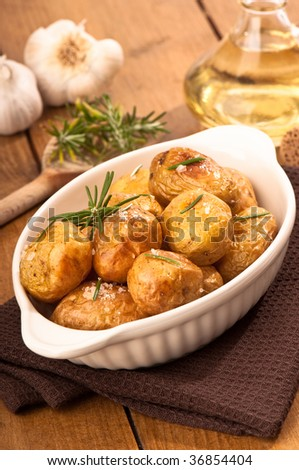 Roasted potatoes with rosemary herb with garlic and olive oil in background - stock photo