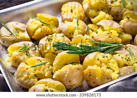 Roasted potatoes with rosemary, pepper and pink sea salt in tray, close up. SIde dish for holiday family dinner - stock photo