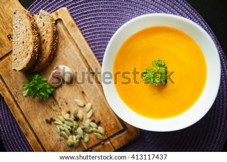 Roasted pumpkin and carrot soup with cream and pumpkin seeds on purple and wooden background - stock photo