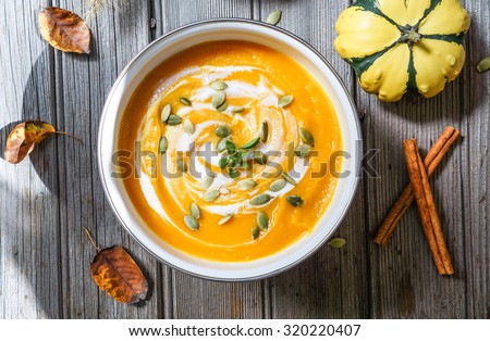 Roasted pumpkin and carrot soup with cream and pumpkin seeds on white wooden background   - stock photo