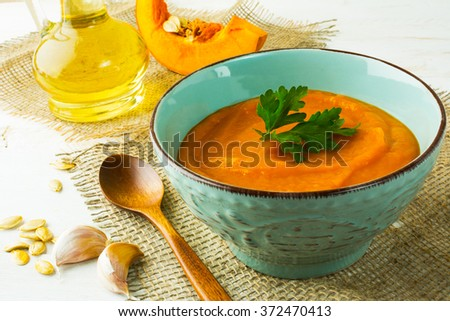 Roasted pumpkin cream soup with parsley in the turquoise cup on burlap, close up. Pumpkin soup. Squash soup. Soup. Creamy soup. Vegetable soup   - stock photo