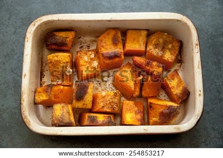 Roasted pumpkin in a ceramic pot on a black slate background - stock photo
