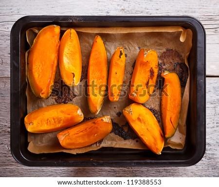 Roasted pumpkin on a baking tray - stock photo