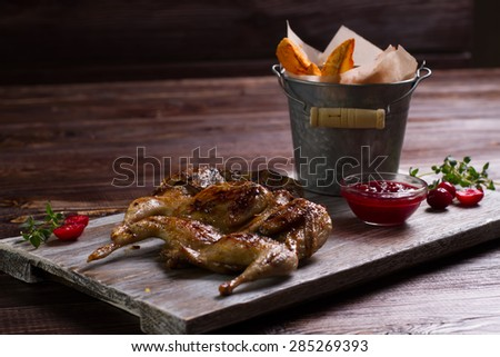 Roasted quail with a garnish on a wooden background. Exclusive dish. - stock photo