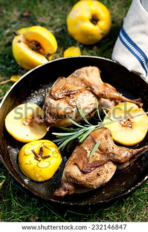 Roasted quails with quince on a cast iron skillet outdoor, vertical - stock photo