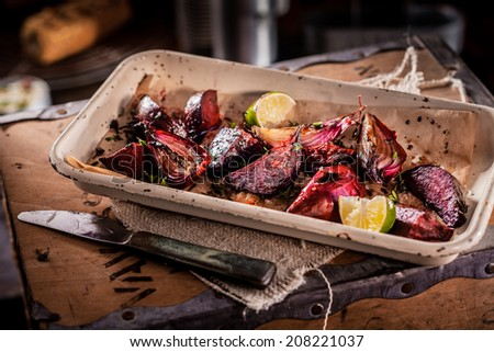 Roasted red onions in an earthenware crock garnished with fresh lemon for a tasty vegetarian or vegan dish or accompaniment to a meal - stock photo