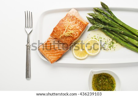 Roasted salmon fillet with asparagus on white. - stock photo