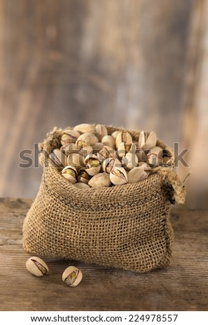 roasted salty pistachios nuts in sack bag,above view - stock photo