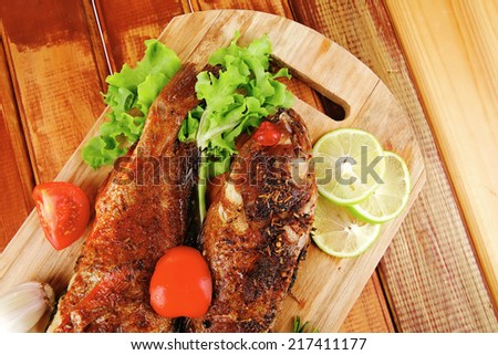 roasted sea fish and castors on wood with tomatoes, lemon and green lettuce salad . shallow dof - stock photo