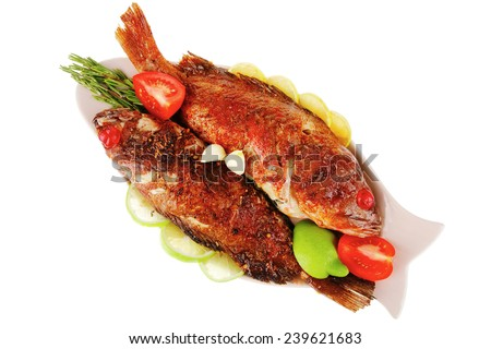roasted sea fish on plate with tomatoes, lemon and rosemary - stock photo