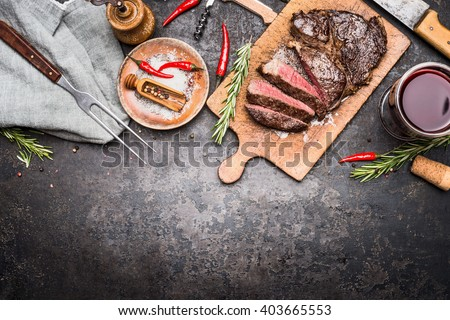 Roasted sliced grill steak on wooden cutting board with wine, seasoning and meat fork on dark vintage metal background, top view, border - stock photo