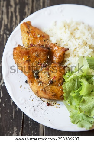 Roasted Spicy Chicken Breasts with Rice Garnish and Lettuce - stock photo