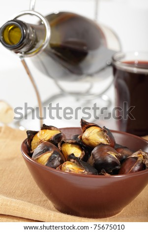 Roasted sweet chestnuts and red wine - stock photo