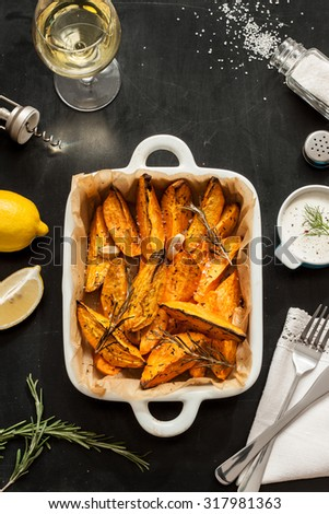 Roasted sweet potatoes in white ceramic dish. Wine, dip, lemon, salt and rosemary around. Black chalkboard as background. Restaurant table scenery from above. - stock photo