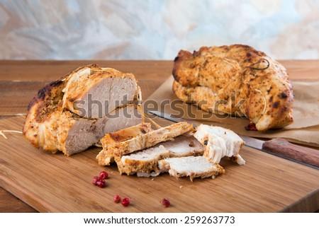 Roasted turkey breast on wooden plank - stock photo