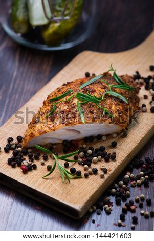 Roasted turkey breast seasoned with rosemary  and  pepper seeds on wooden plank - stock photo