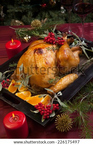 Roasted turkey garnished with sage, rosemary, and red berries in a tray prepared for Christmas dinner. Holiday table, candles and Christmas tree with ornaments.  - stock photo