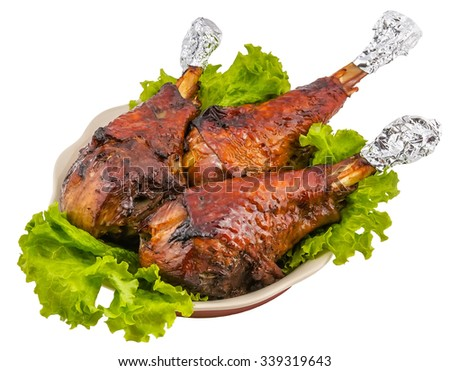 roasted turkey legs garnished with fresh green salad on the plate on white background  - stock photo