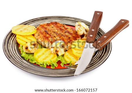Roasted Turkey Steak Garnished with Grilled Sliced Potato, Portabello Mushrooms, Lettuce on Striped Plate with Fork and Knife isolated on white background - stock photo
