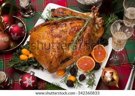 Roasted turkey with fresh fruits, flutes of champagne, Christmas tree, candles, and decorations - stock photo