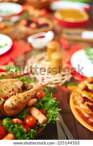 Roasted turkey with vegetables and homemade pie on festive table - stock photo