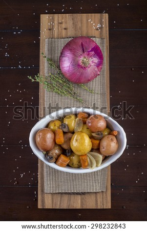 Roasted vegetables dish with potatoes, carrots, mushrooms and onion - stock photo