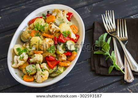 roasted vegetables - zucchini, cauliflower, potatoes, carrots, onions, peppers, on an oval dish on dark wooden background - stock photo