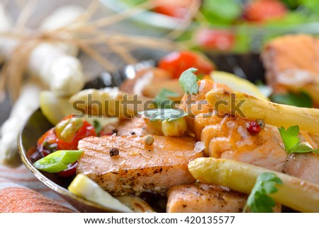 Roasted  white asparagus with fried salmon served in an iron frying pan with a rocket side salad - stock photo