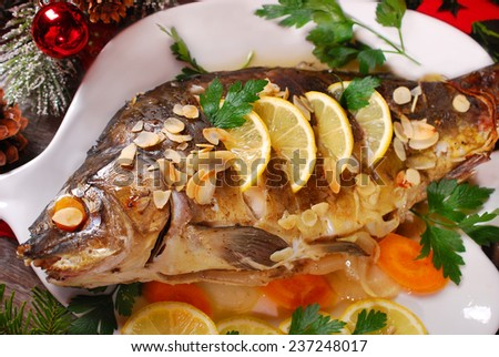 roasted whole carp stuffed with vegetables and almonds on wooden table for christmas - stock photo