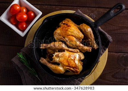 Roasted whole chicken in iron skillet on wooden board, dark texture background - stock photo