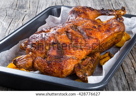Roasted Whole Duck in honey mustard soy glaze in a baked dish with grilled orange slices on an old rustic table , close-up - stock photo
