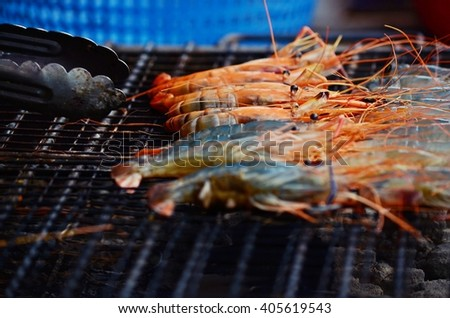 roasting and cooked shrimps on gridiron, shrimp barbecue - stock photo