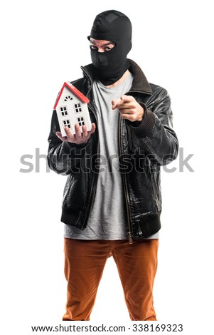 Robber holding a little house - stock photo