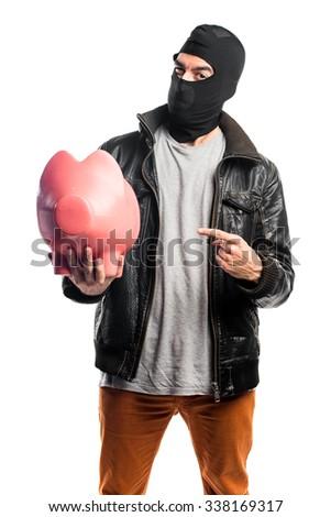 Robber holding a piggybank - stock photo