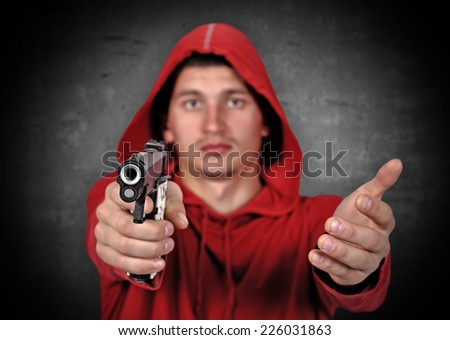 robber holding  gun on a gray background - stock photo