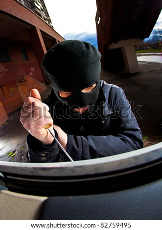 robber in a mask opens a window - stock photo