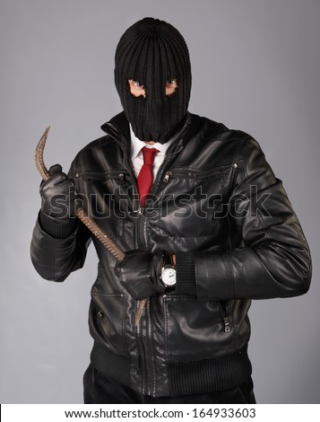 Robber in a mask with a crowbar - stock photo